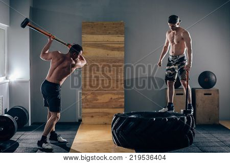 Sledgehammer Tire Hits men workout at gym with hammer and tractor tire, one man standing on tire