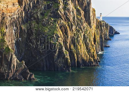 A look at Lighthouse on the cliffs of Neist Point, rugged and rocky coast on the western side Isle of Skye. Famous landmark near Glendale, Skye island, Scotland, United Kingdom, UK, Europe