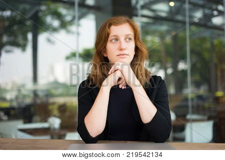 Portrait of pensive woman at cafe with shut down laptop. Female office worker leaning on hands waiting for waiter on her break for lunch. Business lunch and work balance concept