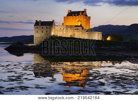 Eilean Donan Castle at Kyle reflecting itself into the water of Loch Duich and loch Alsh, during evening low tide in the Western Highlands of Scotland near Skye, UK.