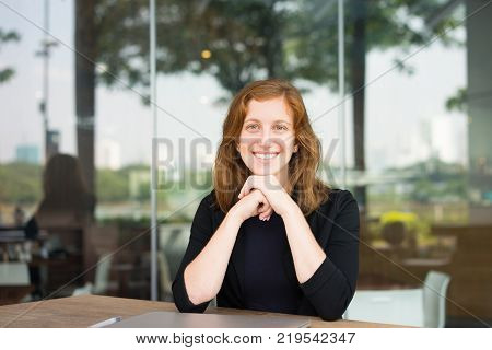 Portrait of happy woman at cafe with shut down laptop smiling at camera. Young female clerk having break. Work balance concept