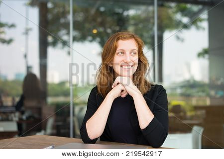 Portrait of happy woman at cafe with shut down laptop smiling and looking away. Young female manager waiting for her colleagues at cafe. Work balance concept