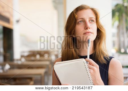 Closeup of dreamy young woman holding notebook, keeping pen on chin and looking far away. Female student drafting essay at cafe. Creative and inspiration concept