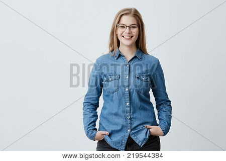People, beauty and lifestyle concept. Shot of attractive sensual blonde woman with spectacles and wide smile dressed in denim shirt smiling broadly being happy to meet her best friend. Joyful nice female