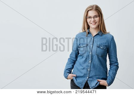Pleased pretty woman with blonde straight hair, dark eyes, stylish eyewear and healthy skin dressed in denim shirt, holding hands in pockets smiling while posing against gray studio wall. People and lifestyle poster