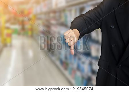 businessman give bad thumbs down on supermarket background