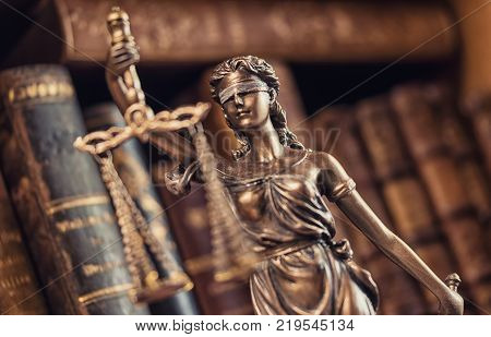 statue of Justice the Roman goddess of Justice in a courtroom with books. ideal for websites and magazines layouts