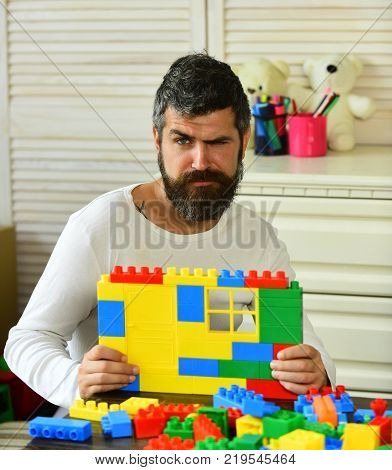Man With Concerned Face Makes Brick Constructions For Kids