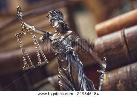 The statue of Justice - lady justice or Iustitia the Roman goddess of Justice with old books. ideal for websites and magazines layouts