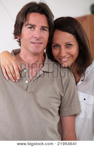 a 35 years old woman putting her arm around her husband