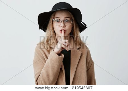 Top secret. Cute blonde young female wearing eyeglasses, coat and hat, with bugged eyes holding a finger on her lips, saying 'shh', asking to keep silent about her big secret, looking at the camera