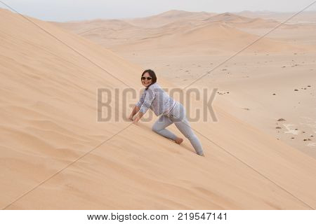 An Indonesian girl climbs Dune 7, the highest sand dune in the world, in Walvis Bay, Namibia