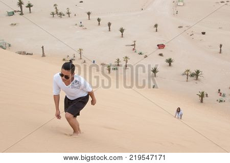 A young Filipino climbs Dune 7, the highest sand dune in the world, in Walvis Bay, Namibia