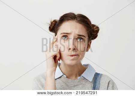 Headshot of adult girl looking up with frown expressing misunderstanding. Cute female student twisting mouth trying to remember her schedule or bothering about exams. Facial expressions