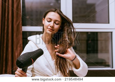 A young girl with long hair dries them with a hair dryer after a shower