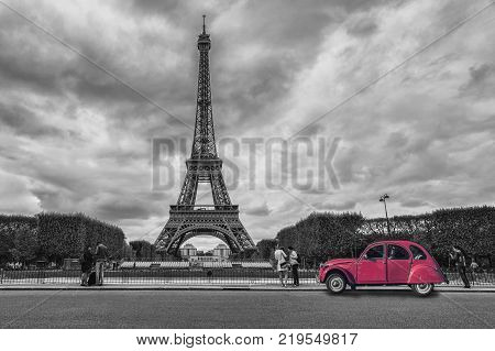 View to the Eiffel tower with a red vintage car in black and white colors colorkey. ideal for websites and magazines layouts