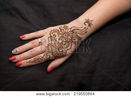 Woman hand with black cute henna mehendi designs