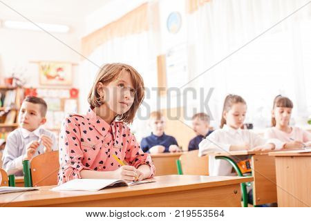 Girl is writing in the copybook on the lesson. 8 years old schoolgirl in the classrom. Interesting shcool life