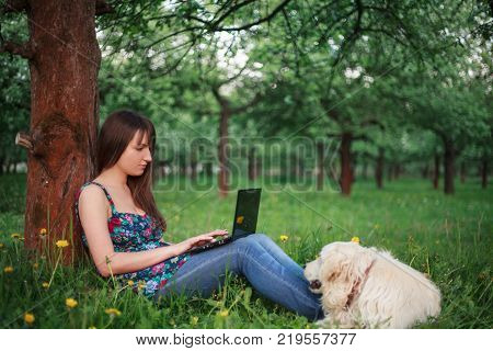 Woman outdoor sitiing with netbook and smiling. Social networking
