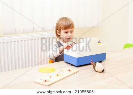 Girl is playing in the role of cashier  in the kindergarten