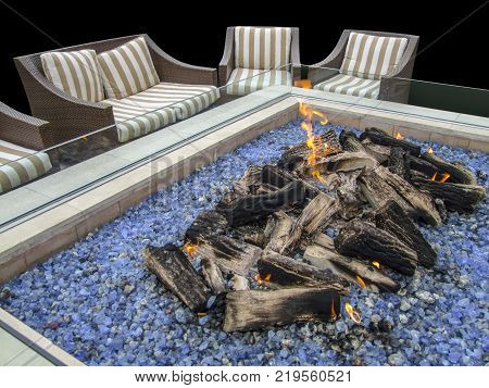 artificial fireplace and chairs in dark ambiance