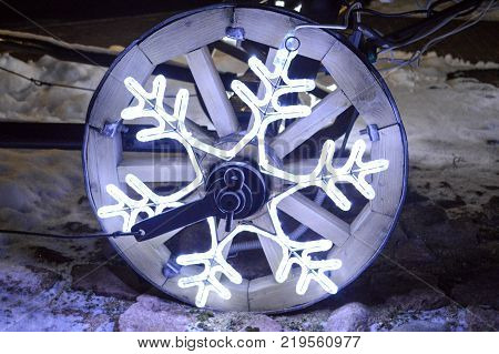 A glowing wheel a Christmas garland in the shape of a snowflake on a wooden wheel of a cart. Christmas decoration wheel.