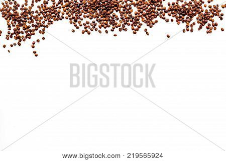 Scattered coffee beans on white table top view copyspace. Coffee background