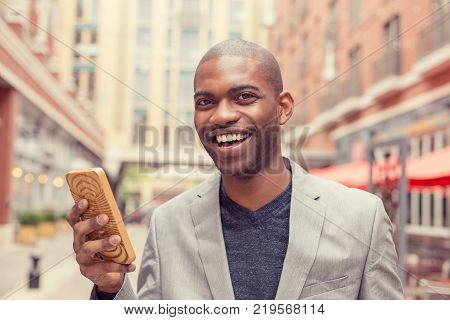 Handsome young man using smart phone outdoors. Casual businessman holding mobile smartphone using app texting sms message wearing jacket