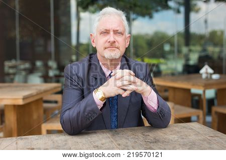 Closeup portrait of serious senior handsome man looking at camera with his hands clasped and sitting at table in outdoor cafe