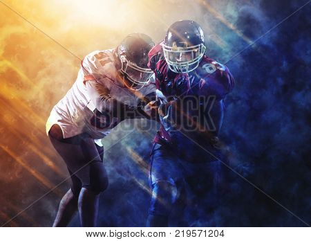 American football players in action at night game time on the field with flame effects and particles