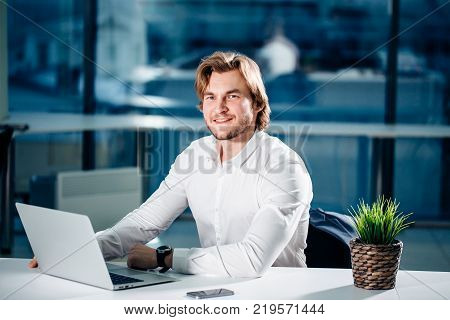 Business man working on laptop computer with business document, graph diagram and calculator on office table