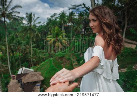 Happy couple walking at the rice terraces, holds hands. Traveling at Bali. Honeymoon summer travel at Indonesia.