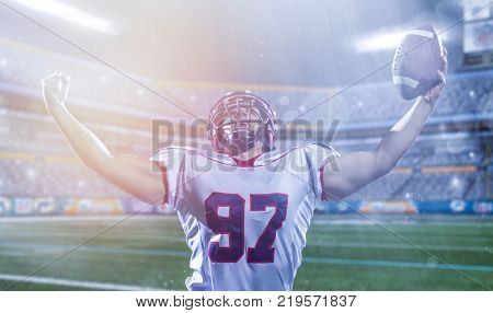 american football player celebrating after scoring a touchdown on big modern stadium field with lights and flares at night