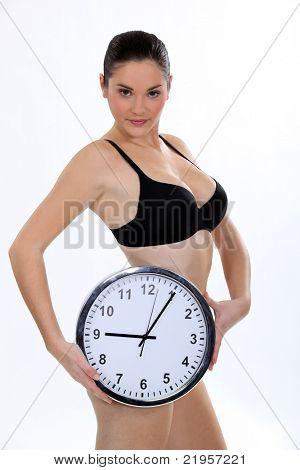 Mulher sutiã segurando o relógio