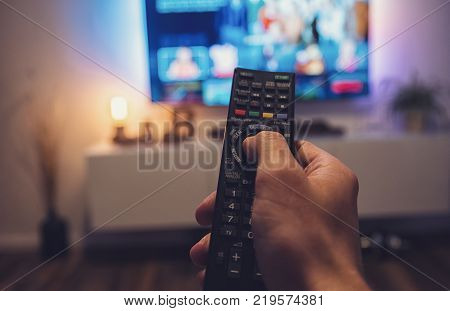 POV-Shot from a mans hand holding a TV Remote control to ZAP on tv at home. ideal for websites and magazines layouts