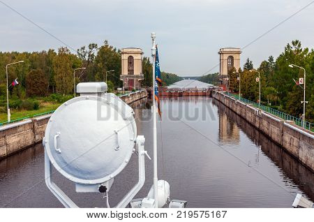 MOSCOW REGION - SEPTEMBER 10 2017: River cruise ship on the highest level of the river gateway. Searchlight and flagpole in the foreground