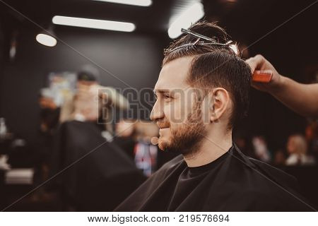 Barbershop. man in a hairdresser is preparing barber to cut hair with hairpin clips.