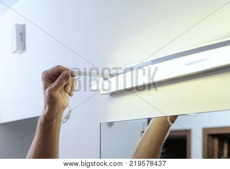 Installing the lamp above the mirror. A man is removing a protective tape from the lamp after installing it.
