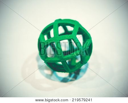 Abstract object of a green color printed by 3d printer on white background. Fused deposition modeling, FDM. Progressive modern additive technology. Concept of 4.0 industrial revolution