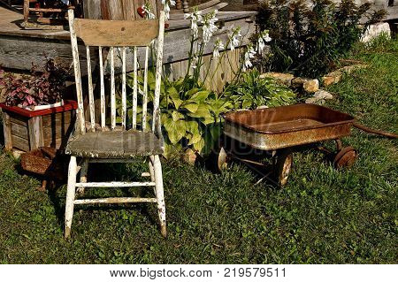 An old rickety wooden chair and a rusty child's wagon are located in front of a weathered porch.