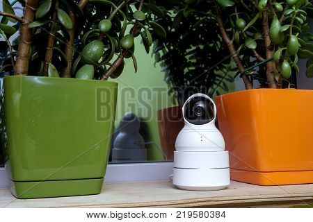 security camera operating in home. Funny surveillance camera in the form of a robot. surveillance camera stands between flowerpots on the windowsill of the house