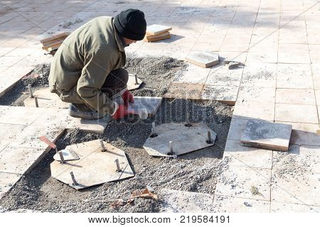 Worker puts sidewalk tile . In the park in nature
