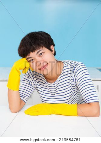 Smiling pretty Asian housewife resting after cleaning and sitting at table. Calm young maid in rubber gloves doing housework. Stereotypical woman concept