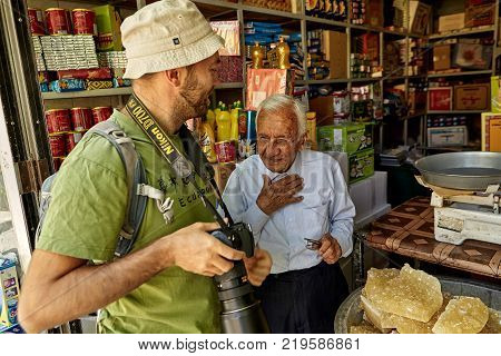 Yazd Iran - April 22 2017: The tourist talks with an elderly Iranian grocer in the interior of a grocery store.