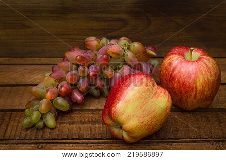Apples and grapes on a wooden rustic background. Still life for thanksgiving with autumn fruits. Top view. Selective focus