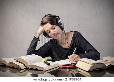 lächelnd Student Musikhören beim überarbeiten
