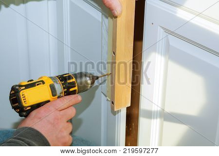 Worker use drill to repair furniture and drills the cabinet door a cordless screwdriver, close up.