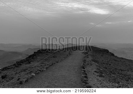 White and black sunrise in negev desert in israel. Mountain road to colorful horizon view. Tourism in national park valley with stones, rocks, sand beautiful red sun