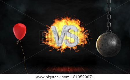 3d rendering of a concrete letters VS surrounded by fire stand between a red celebration balloon and a wrecking ball. Leisure or work. Party against business. Choose between activities.