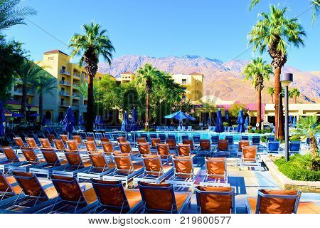 December 19, 2017 in Palm Springs, CA:  Poolside lounge chairs and desert gardens surrounding a pool taken at the Renaissance Hotel in Palm Springs, CA where resort guests can sunbathe, swim, and relax at the pool with views of the desert and mountains